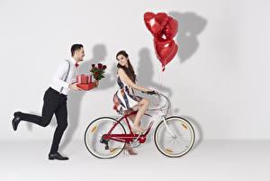 Картинка День святого Валентина Мужчины Розы Вдвоем Шатенка Велосипеде Подарки Воздушным шариком Сердце молодые женщины