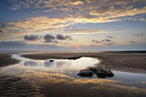 Фото Великобритания Пейзаж Рассветы и закаты Побережье Вода Небо Камни Облака Пляж Dunraven Bay Wales Природа
