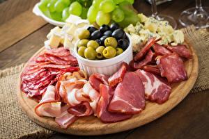 Фото Мясные продукты Ветчина Колбаса Овощи Оливки Разделочная доска Пища