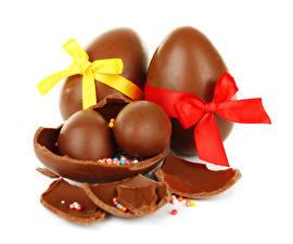 Фотография Праздники Пасха Шоколад Сладости Белый фон Яйца Бантик Еда
