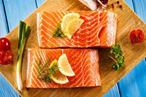Фотография Морепродукты Рыба Лимоны Разделочная доска Еда