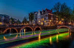 Картинка Амстердам Нидерланды Дома Реки Мосты Ночь Уличные фонари Скорость
