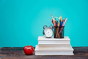 Фото Яблоки Часы Будильник Книга Карандаши Цветной фон