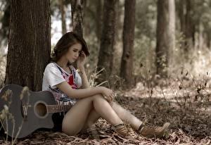 Картинка Азиаты Сидящие Гитара Ствол дерева Красивые Ноги Девушки