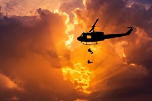 Картинка Вертолеты Рассветы и закаты Десант Силуэт Лучи света Облака Американские Bell UH-1 Iroquois Авиация Армия