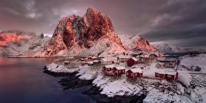 Картинка Норвегия Здания Горы Берег Вечер Скале Снега Reine Nordland Города