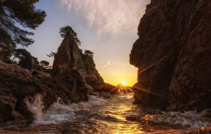 Картинка Побережье Рассветы и закаты Волны Скала Лучи света Солнце Природа