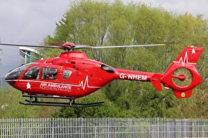 Фотографии Вертолеты Красный Сбоку Летящий G-NHEM Eurocopter EC-135-T2