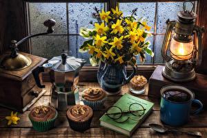 Фото Натюрморт Нарциссы Керосиновая лампа Пирожное Кофе Чайник Капкейк кекс Книга Очки Кружка Пища