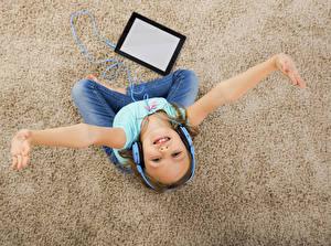 Картинки Планшетный компьютер Девочки Руки Наушники Смотрит Ковер Ребёнок