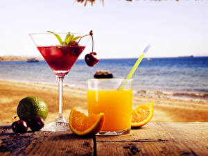 Картинки Напитки Сок Апельсин Вишня Море Стакан Бокалы Вдвоем Еда