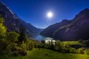 Фотографии Швейцария Горы Озеро Пейзаж Солнце Кусты Lake Klontal Glarus Природа
