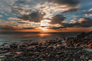 Картинки Пейзаж Исландия Рассветы и закаты Берег Камень Небо Облака Природа