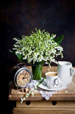 Фото Натюрморт Ландыши Часы Кофе Черный фон Чашка Кувшин Цветы