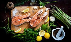 Фотографии Морепродукты Рыба Лимоны Овощи Чеснок Приправы Разделочная доска