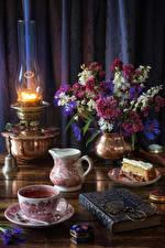 Фотография Натюрморт Керосиновая лампа Букеты Чай Пирожное Чашка Кувшин Книга Очки Еда