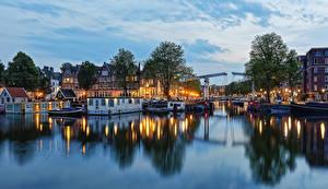 Картинки Амстердам Нидерланды Здания Речка Вечер Причалы Мосты Деревья Города