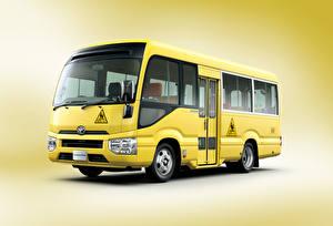 Картинки Автобус Цветной фон Желтый 2016-17 Toyota Coaster School Bus Авто
