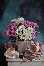 Фотографии Натюрморт Букет Хризантемы Часы Кофе Кувшины Книга Чашка Еда Цветы