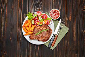 Фото Вторые блюда Мясные продукты Картофель фри Овощи Нож Доски Тарелка Кетчуп Вилка столовая