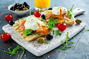Картинка Бутерброды Хлеб Рыба Оливки Помидоры Разделочная доска Яичница Еда