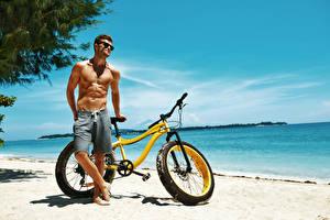 Картинка Мужчины Побережье Велосипед Очки Мускулы Красивые Пляж Спорт