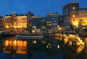 Фото Нидерланды Амстердам Здания Мосты Пирсы Вечер Речные суда Водный канал Уличные фонари