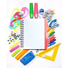 Фотография Канцелярские товары Белом фоне Блокнот Шариковая ручка Карандаш