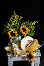 Картинка Натюрморт Дыни Подсолнухи Черный фон Продукты питания