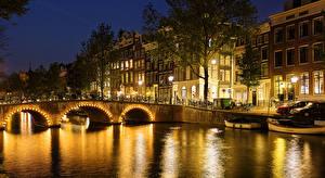 Картинка Нидерланды Амстердам Здания Мосты Причалы Водный канал Ночь Уличные фонари Деревья