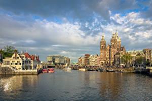 Картинки Нидерланды Амстердам Здания Речка Пирсы Речные суда Небо
