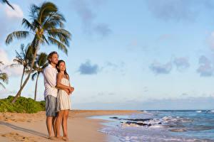 Фотографии Побережье Мужчины Влюбленные пары Небо Двое Улыбка Объятие Пляже молодые женщины