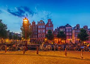 Фотографии Нидерланды Амстердам Дома Вечер Забор Уличные фонари Велосипед