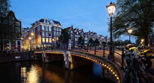 Фотографии Нидерланды Амстердам Здания Мосты Вечер Водный канал Уличные фонари Города