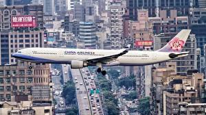 Обои для рабочего стола Самолеты Пассажирские Самолеты Здания Airbus Летят Сбоку A330-300 Авиация