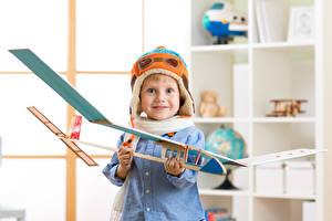Фотографии Самолеты Игрушки Мальчики Смотрит Шапки Улыбка Ребёнок
