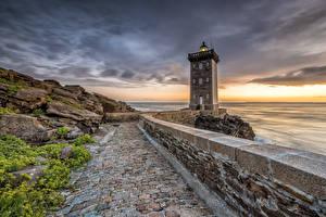 Картинка Франция Рассвет и закат Берег Маяки Камни Забора Leuchtturm Kermorvan Природа