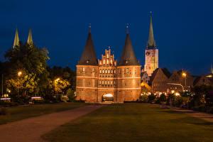 Фото Германия Дома Ворота Газон Уличные фонари Ночью Luebeck Holstentor город
