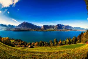 Картинка Швейцария Пейзаж Горы Озеро Побережье Осень Здания Луга Lake Thun