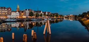 Фото Германия Здания Речка Пирсы Вечер Речные суда Luebeck Города