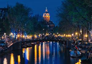 Фотографии Нидерланды Амстердам Дома Мосты Причалы Водный канал Уличные фонари Ночь
