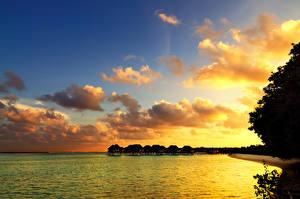 Фотографии Тропики Мальдивы Рассветы и закаты Море Небо Бунгало Облака