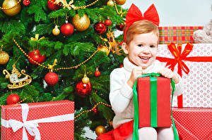 Картинки Новый год Праздники Новогодняя ёлка Девочки Улыбка Подарки Сидит Шарики Ребёнок