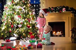 Фото Новый год Праздники Елка Двое Мальчики Девочка Шапки Подарки Дети