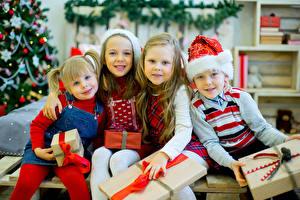 Фото Рождество Праздники Девочки Мальчики Улыбка Шапки Подарки Ребёнок