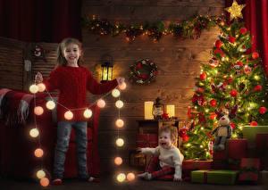 Обои Рождество Праздники Девочка Грудной ребёнок Две Елка Улыбка Электрическая гирлянда Подарки Шар Фонари ребёнок