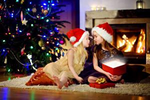 Фото Рождество Праздники Девочка Двое В шапке Подарков Елка ребёнок
