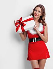 Фотографии Новый год Белый фон Шатенка Улыбка Платья Подарок молодая женщина