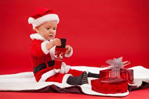 Картинки Праздники Рождество Грудной ребёнок Санта-Клаус Униформа Шапки Подарки Красный фон Ребёнок