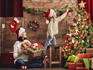 Фотографии Праздники Рождество Доски Новогодняя ёлка Девочки Шапки Подарки Улыбка Шар Ребёнок Девушки